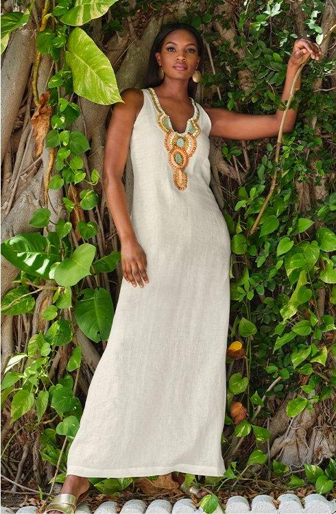 model wearing a white sleeveless maxi dress with multicolored embroidery along the neckline.