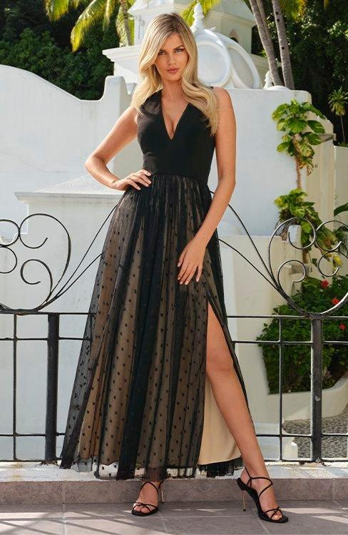 model wearing a black and tan overlay side slit sleeveless gown.