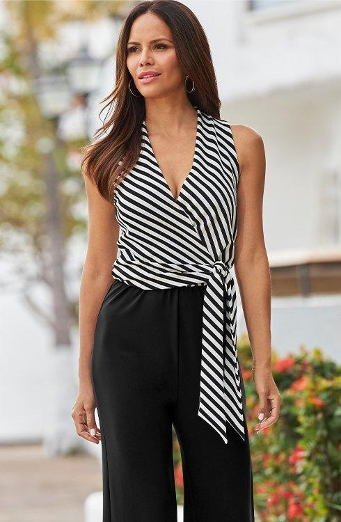 model wearing a black and white striped tie-waist jumpsuit with solid black pants.