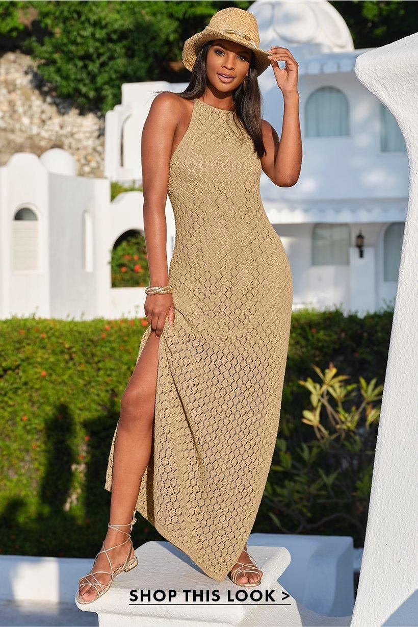 model wearing a tan high-neck sleeveless knit maxi dress, lace-up metallic sandals, and gold embellished cowboy hat.
