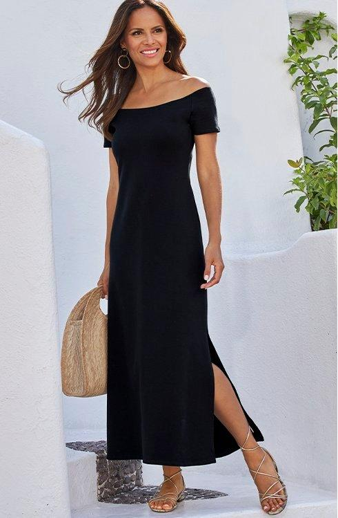 model wearing a black off-the-shoulder short sleeve maxi sport dress while holding a straw bag.