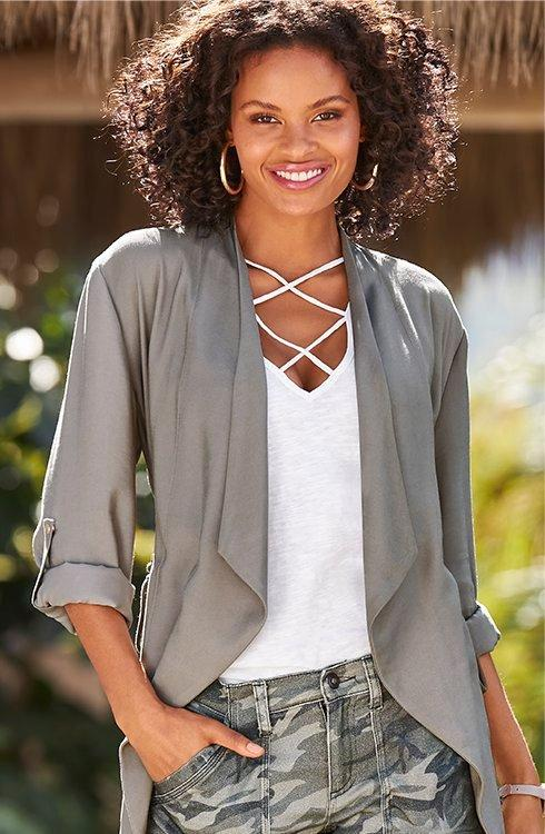 model wearing a lightweight gray cascading jacket, white x-neck top, and camo print denim shorts.