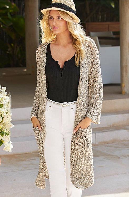 model wearing a beige crochet duster, black henley tank top, white jeans, and straw hat.