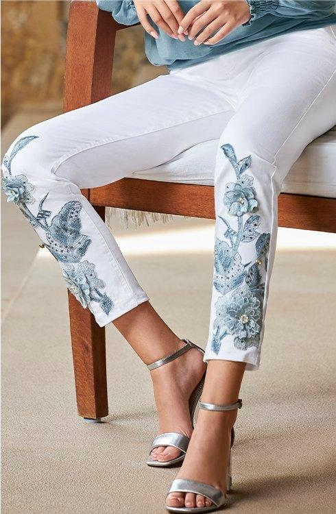 model wearing white jeans with blue embellishments.