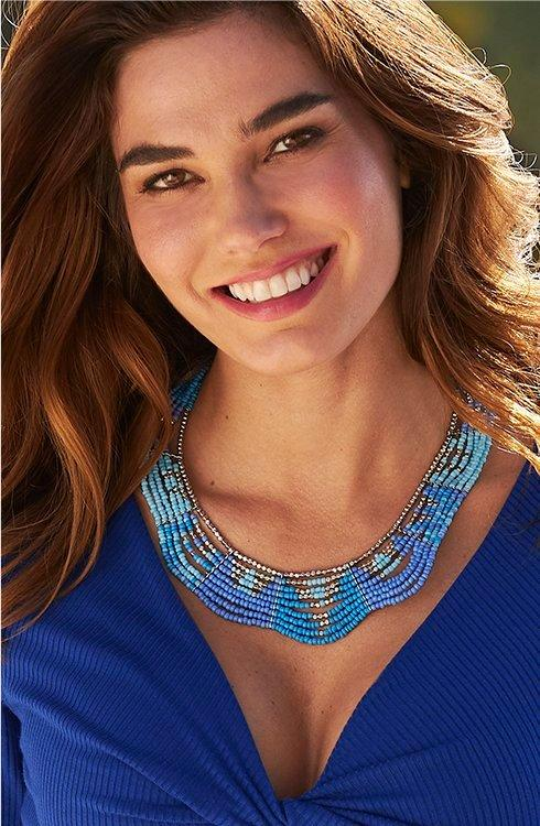 model wearing a blue beaded layered necklace.