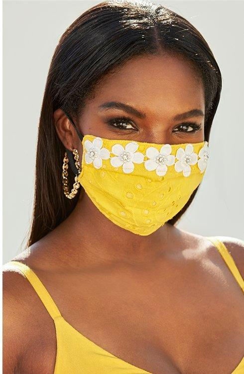 model wearing a yellow face mask embellished with white daisies.
