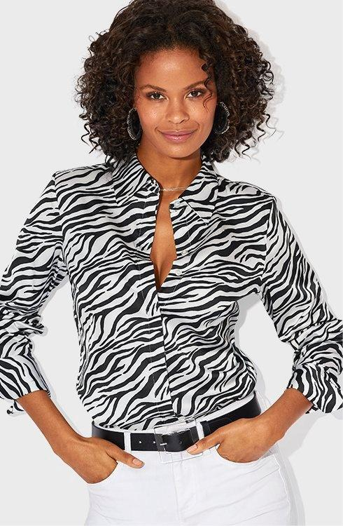 model wearing a black and white zebra print button down top, black belt, and white jeans.