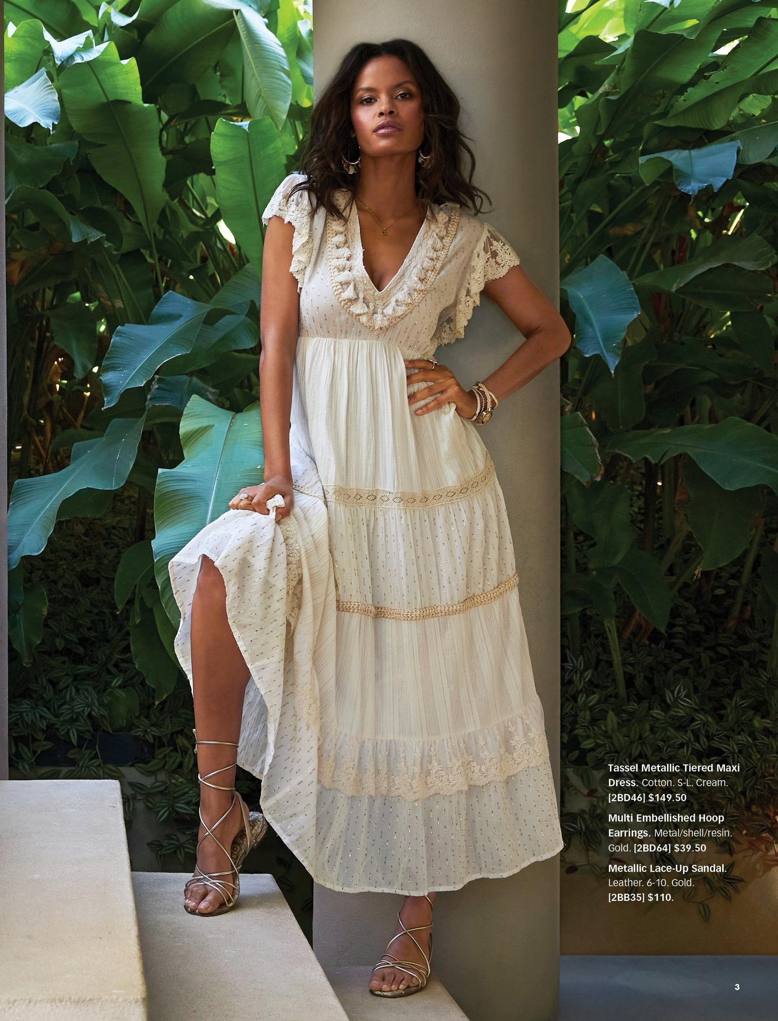 model wearing a cream colored tassel embellished metallic tiered short-sleeve maxi dress, embellished hoop earrings, and gold lace-up sandal.