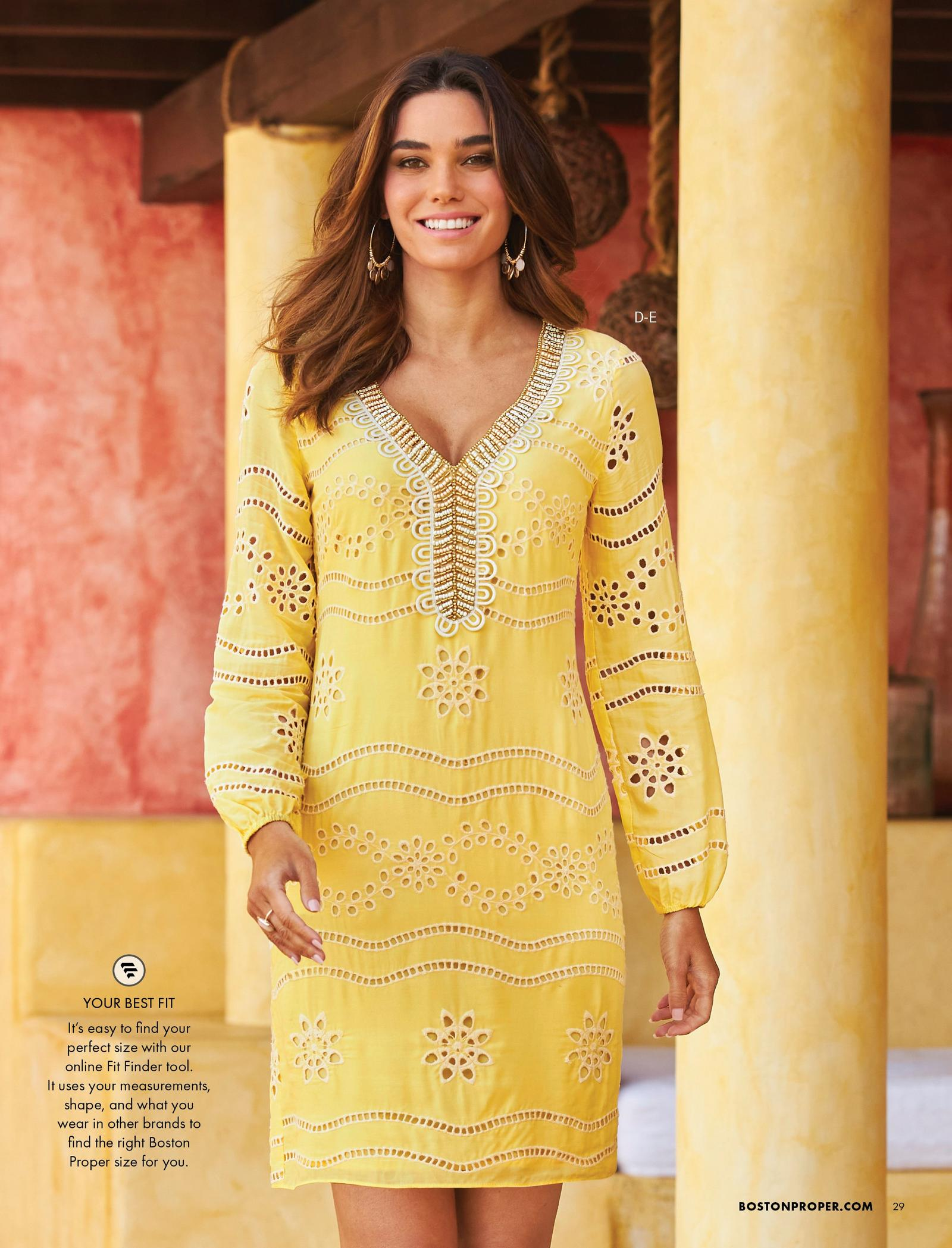 model wearing a yellow eyelet embellished shift dress and gold embellished hoop earrings.