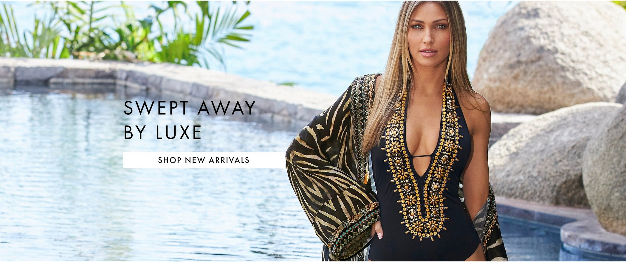 model wearing a black and gold embellished one-piece swimsuit and an embellished animal print duster cover-up.