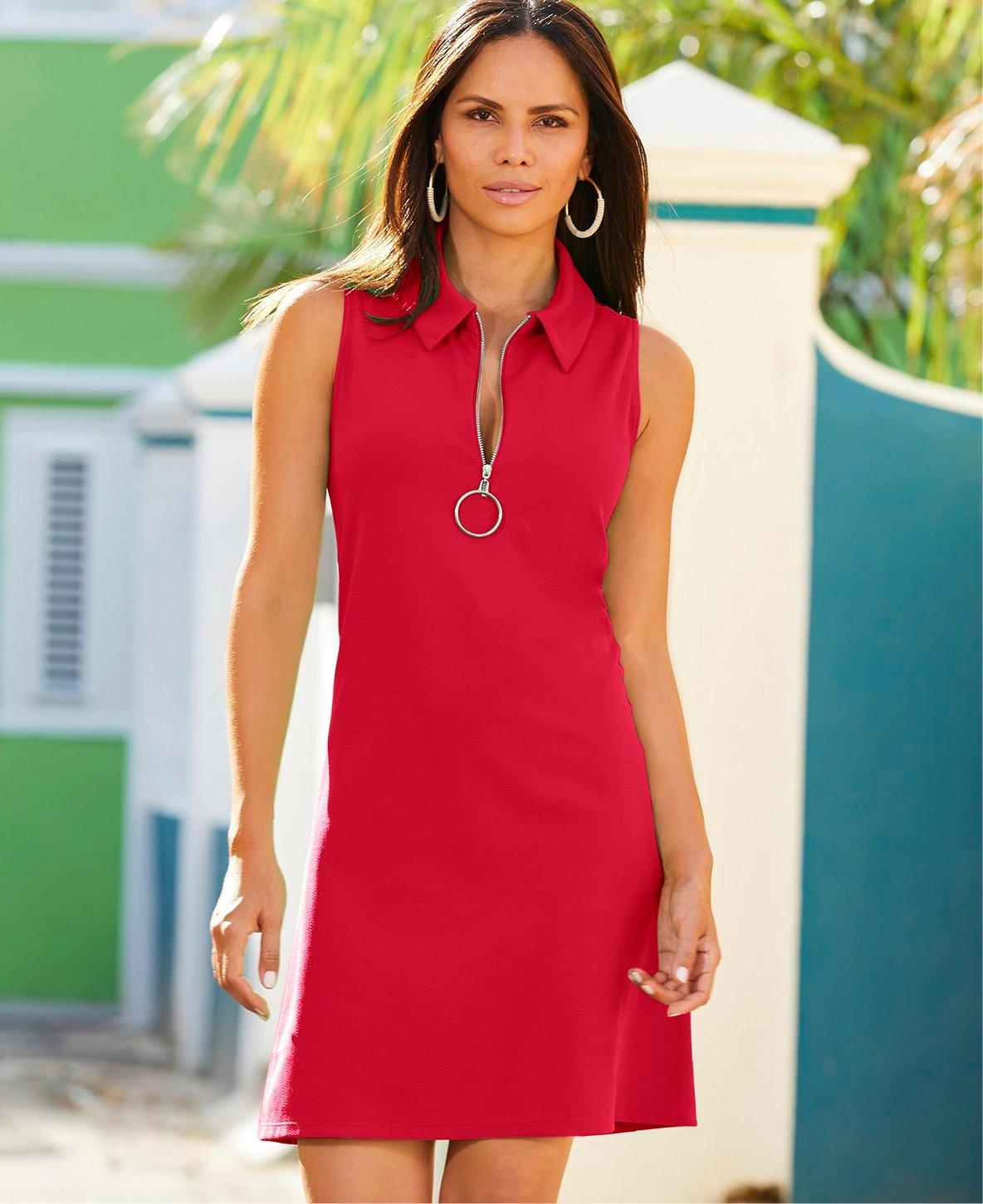 model wearing a red sleeveless collared sport dress and gold hoop earrings.