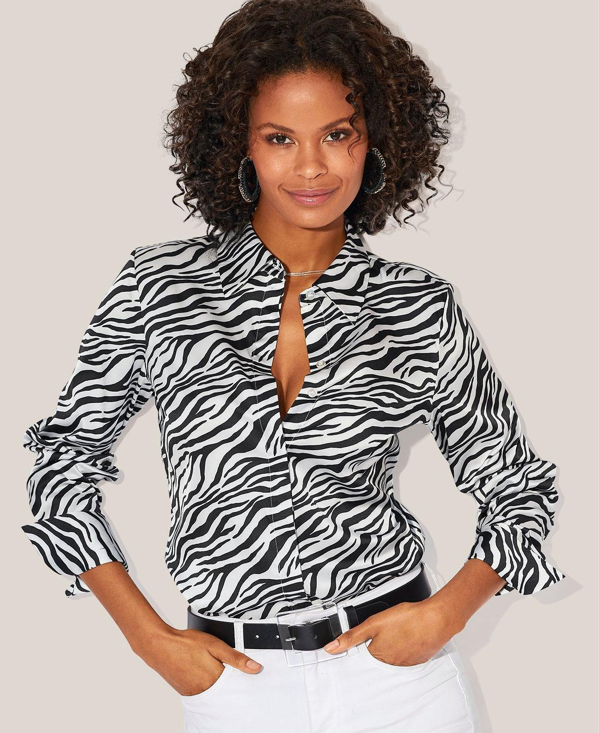 model wearing a black and white zebra striped button-down top, black belt, and white jeans.