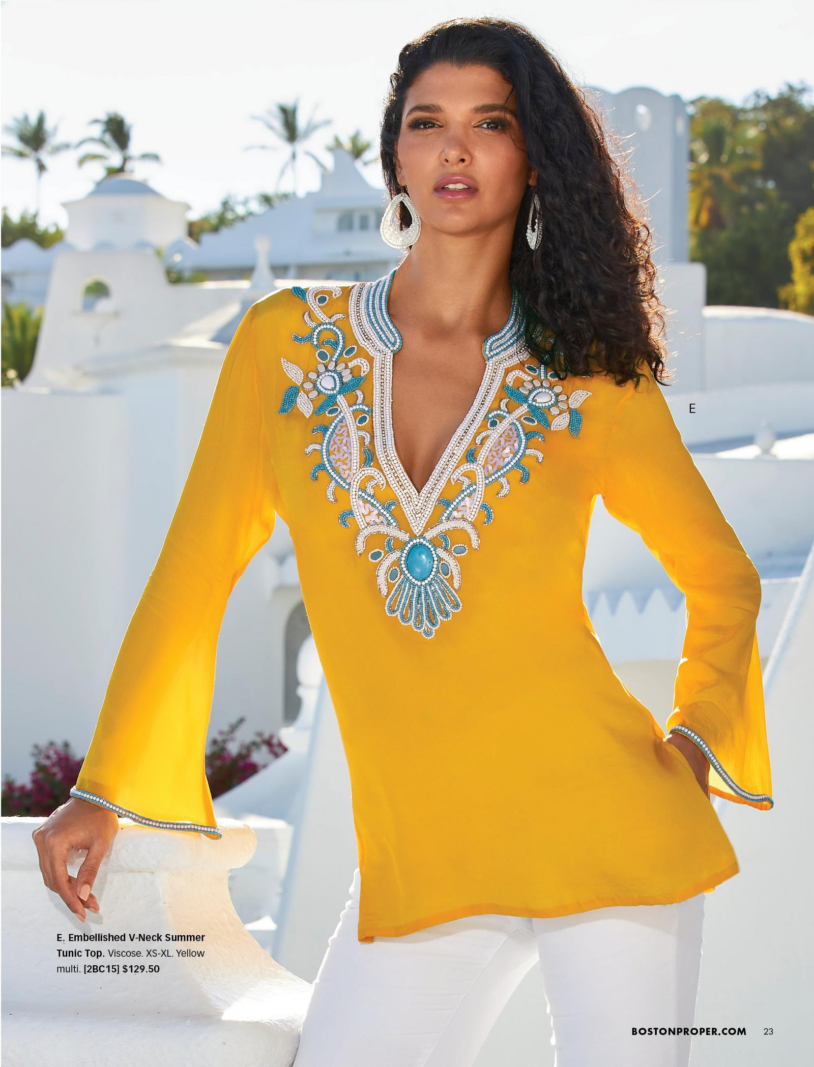 model wearing a yellow long-sleeve tunic with turquoise stone embellishments and white jeans.