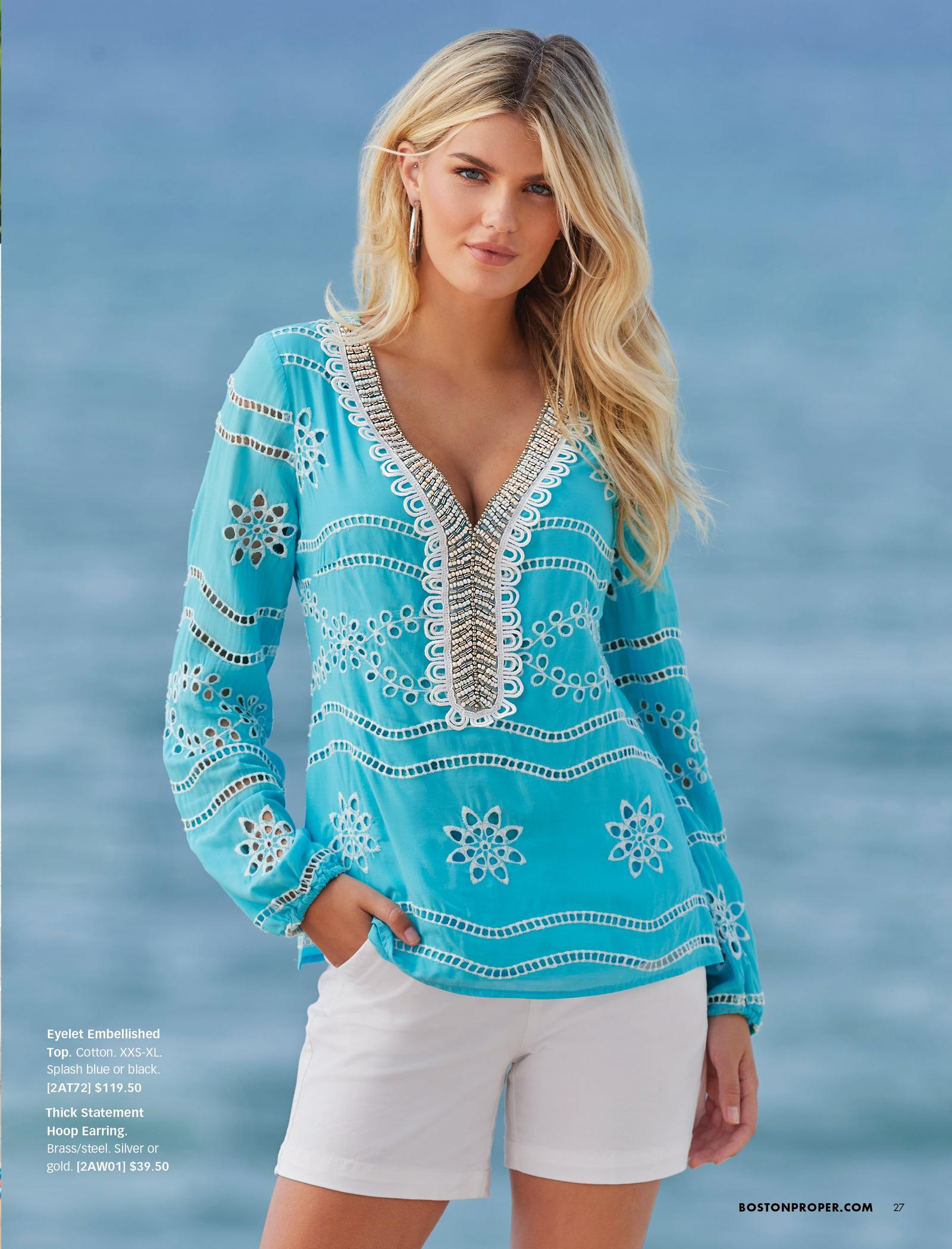 model wearing a light blue and white eyelet long-sleeve tunic top with silver embellishments and white shorts.