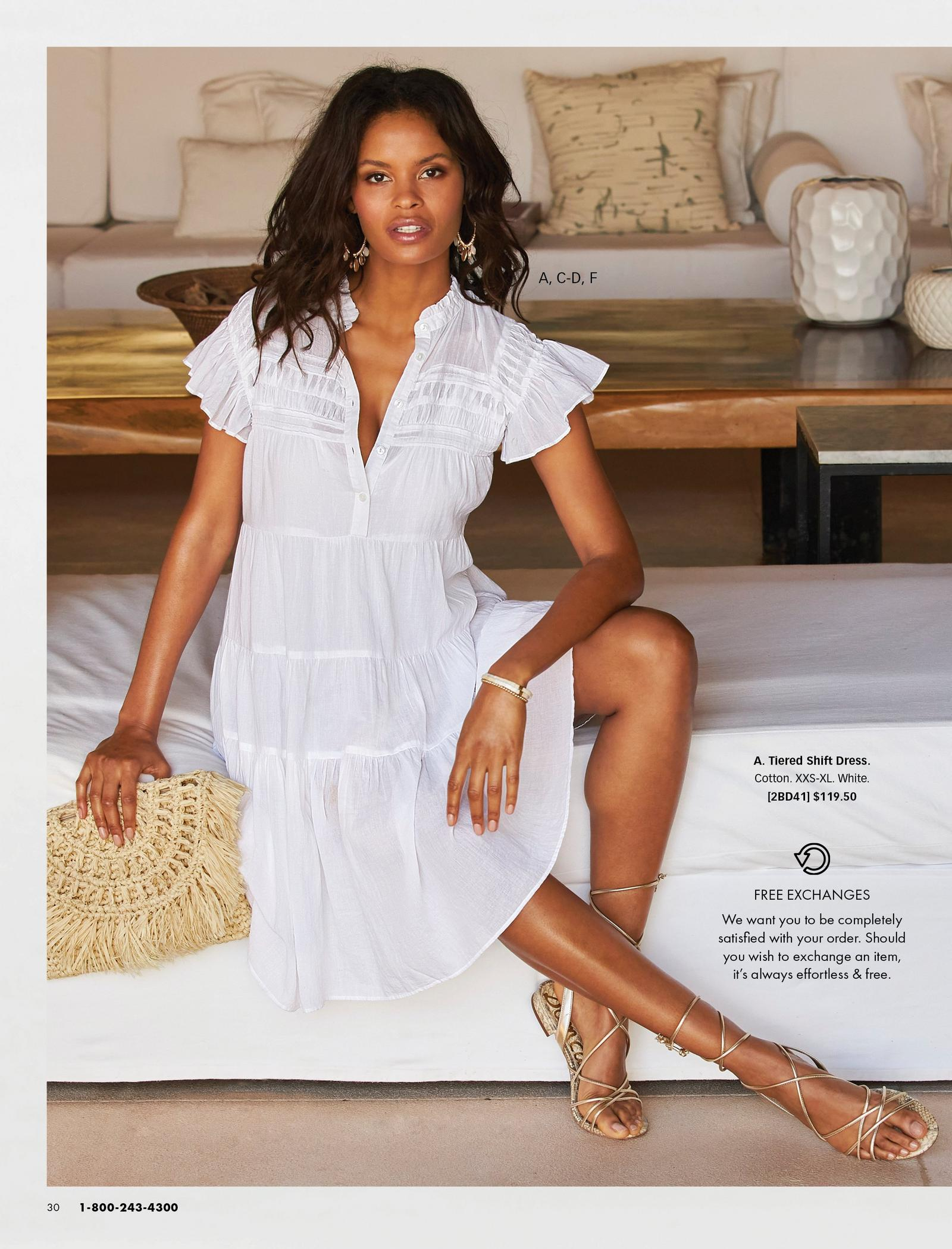 model wearing a white tiered sleeveless shift dress, gold lace-up sandals, and holding a straw clutch.