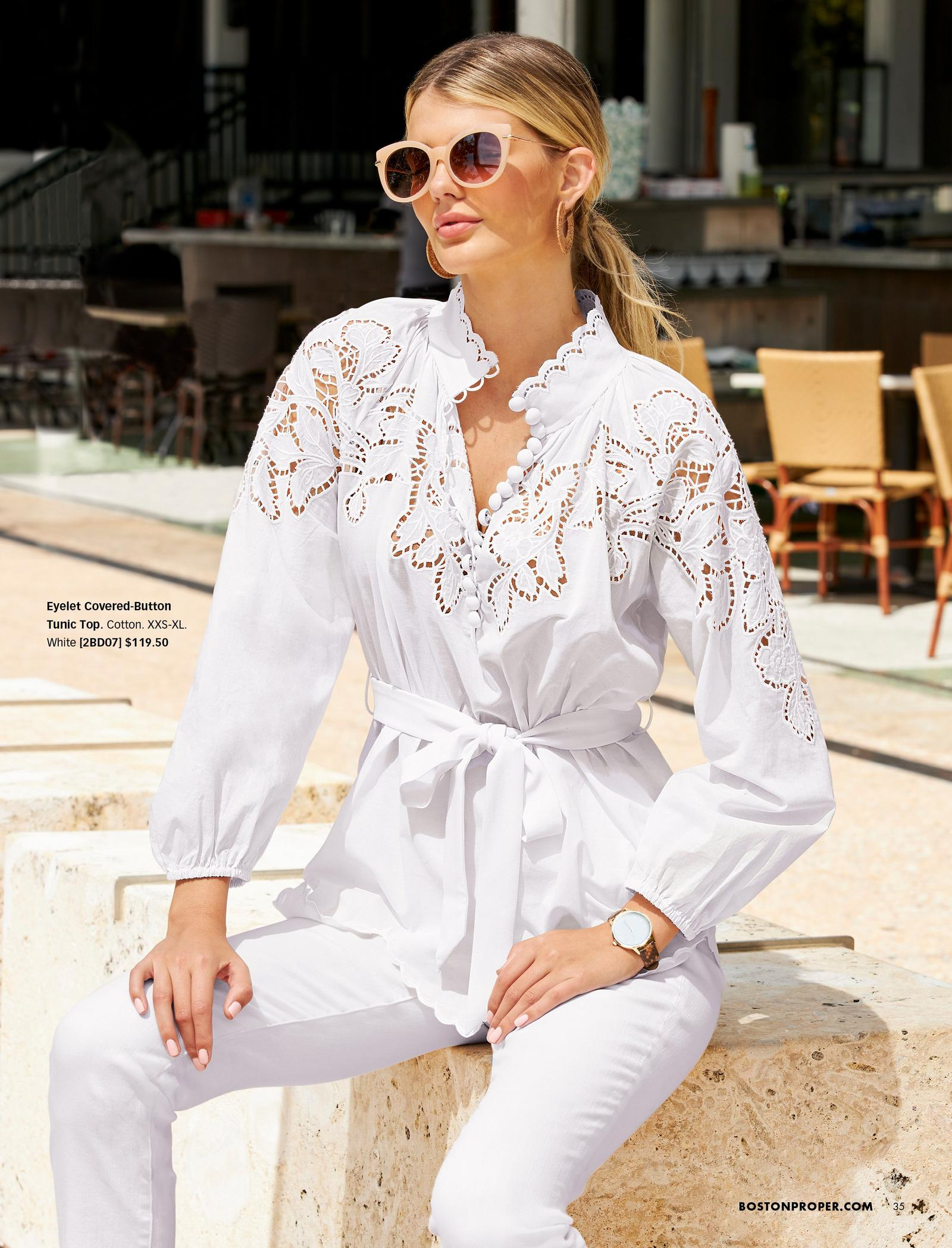 model wearing a white eyelet covered-button long-sleeve tunic top that ties at the waist, white jeans, and sunglasses.