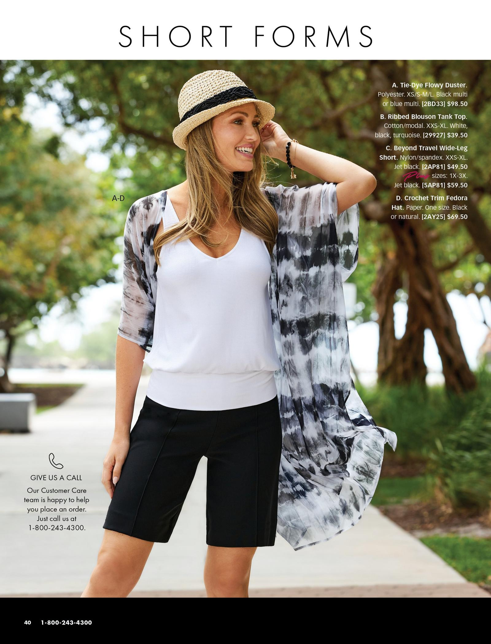model wearing a black and white tie-dye duster, white blouson tank top, black shorts, and a straw hat with black lace detail.