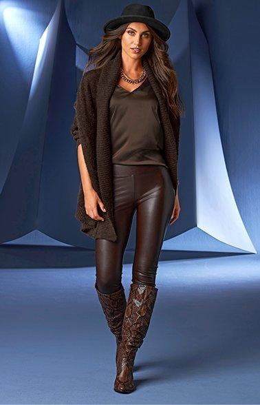 model wearing a dark brown cardigan, dark brown v-neck tank top, dark brown faux leather leggings, brown knee length boots, and black hat.