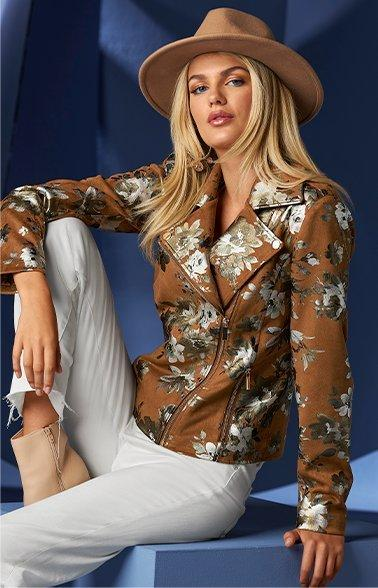 model wearing a brown faux suede jacket with silver foil flowers, white jeans, tan booties, and a tan floppy hat.