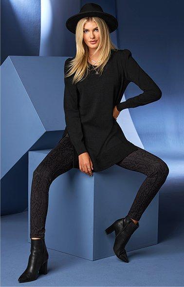 model wearing a black puff-sleeve tunic, black leggings, black block heel leather booties, and a black fedora.