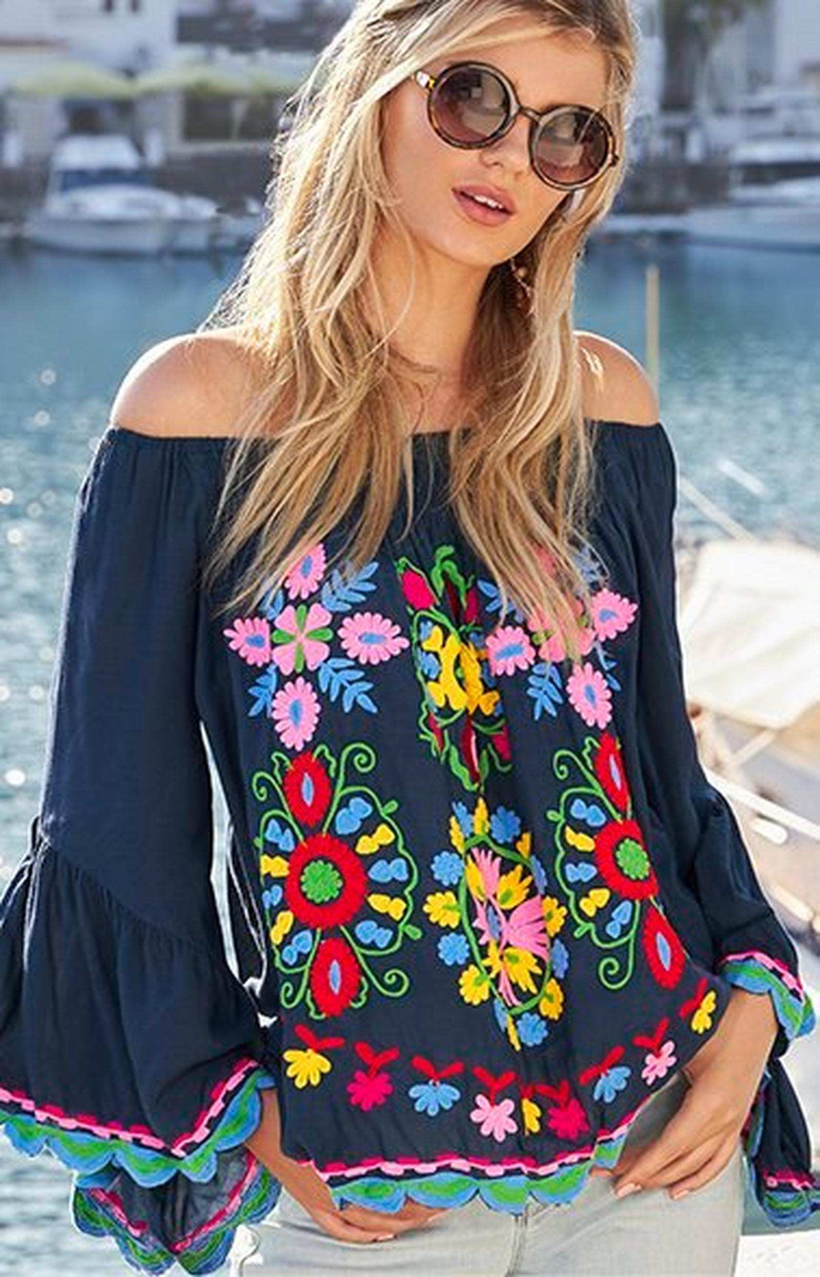 model wearing a navy off-the-shoulder flare-sleeve top with multicolored floral embroidery, jean shorts, and sunglasses.