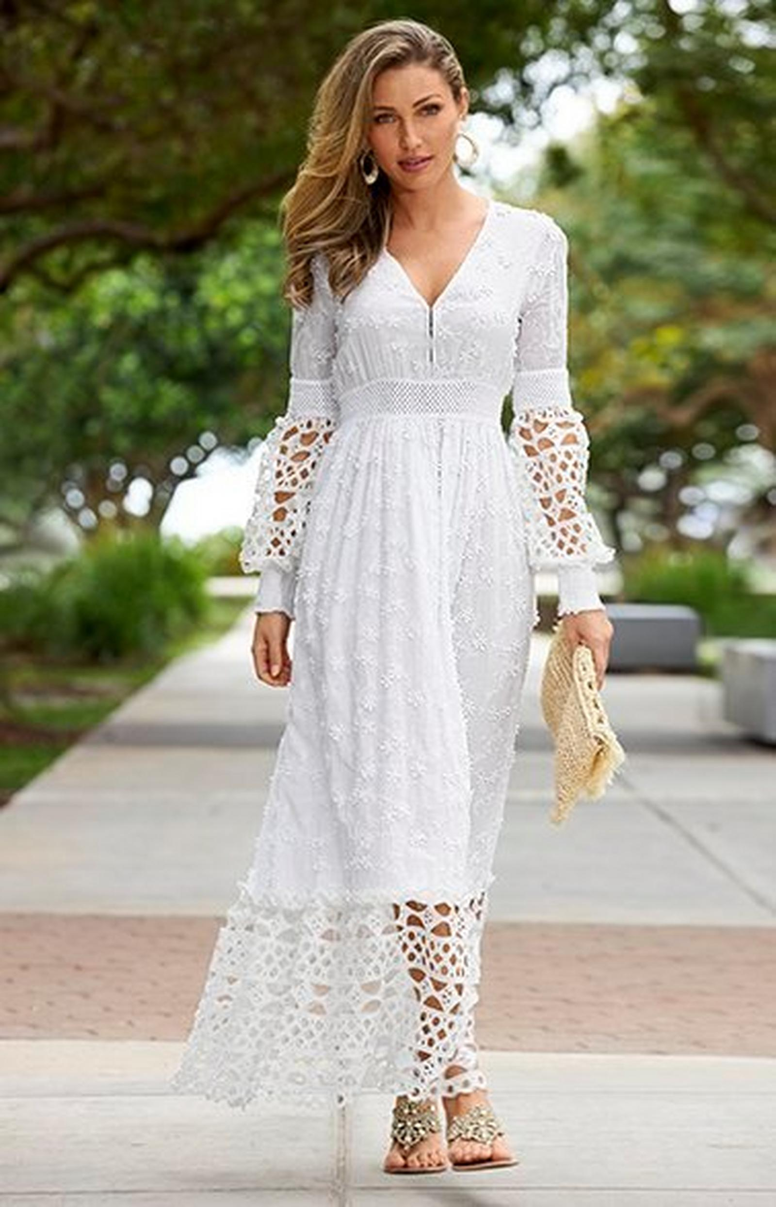 model wearing a white lace long-sleeve v-neck maxi dress, jeweled sandals, and holding a straw clutch.
