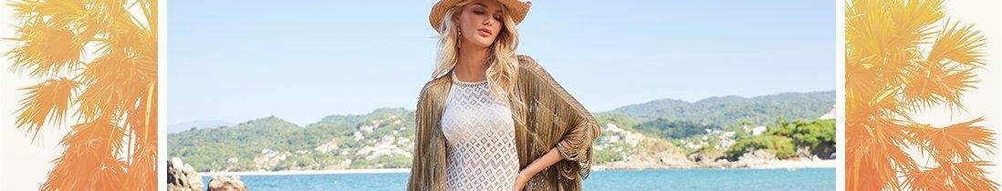 model wearing a taupe fringe duster cover-up, white crochet high-neck one-piece swimsuit, and gold embellished cowboy hat.