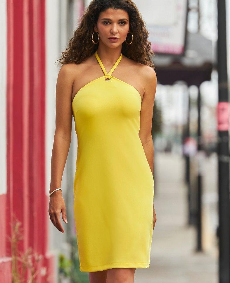 model wearing a yellow halter dress.