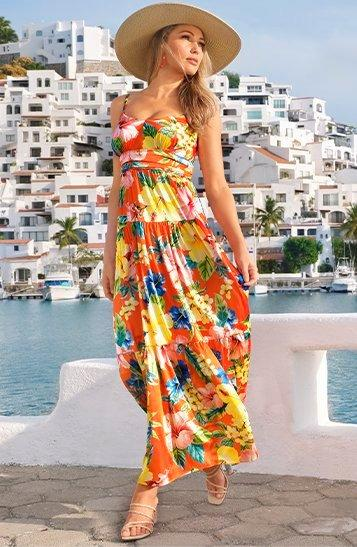 model wearing a multicolored floral sleeveless v-neck maxi dress and straw hat.