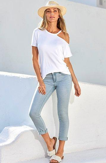 model wearing a white off-the-shoulder white tee, light wash jeans, white sandals, and straw hat.
