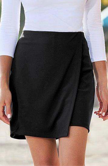 model wearing a black skort and white top.