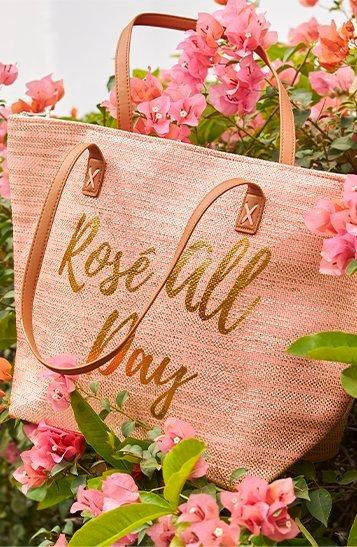 large pink beach bag with text: rose all day.