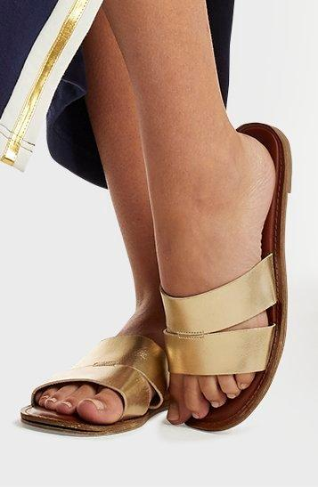 model wearing gold double-banded sandals.
