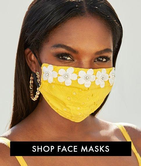 model wearing a yellow face mask with white daisy embellishments.