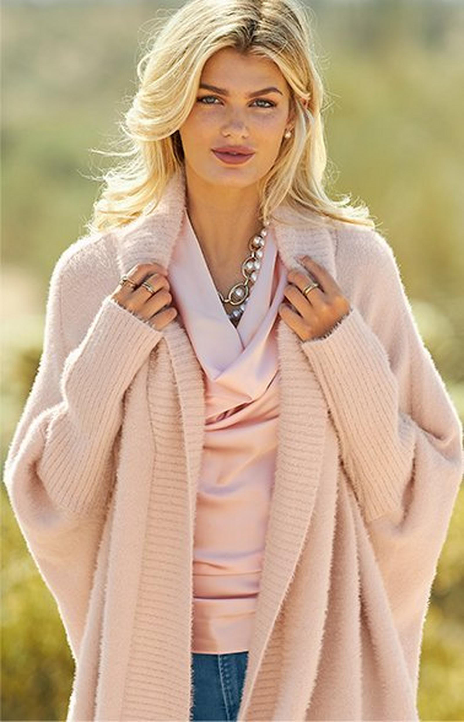 model wearing a light pink plush cardigan and light pink cowl neck tank top.