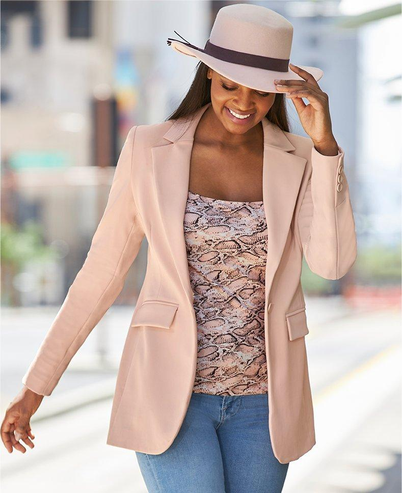 model wearing a light pink blazer, pink snake print top, jeans, and fedora hat.