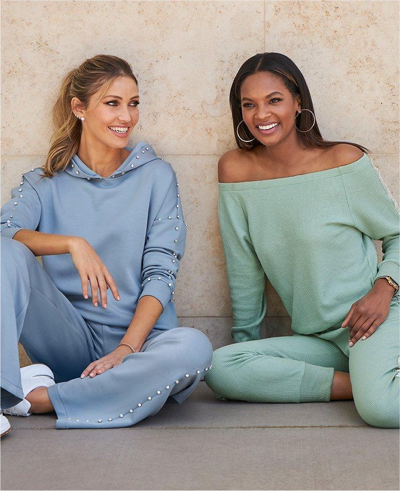 left model wearing a light blue sweatshirt and sweatpants set with white sneakers. right model wearing a sage green off-the-shoulder sweater with matching joggers and white sneakers.