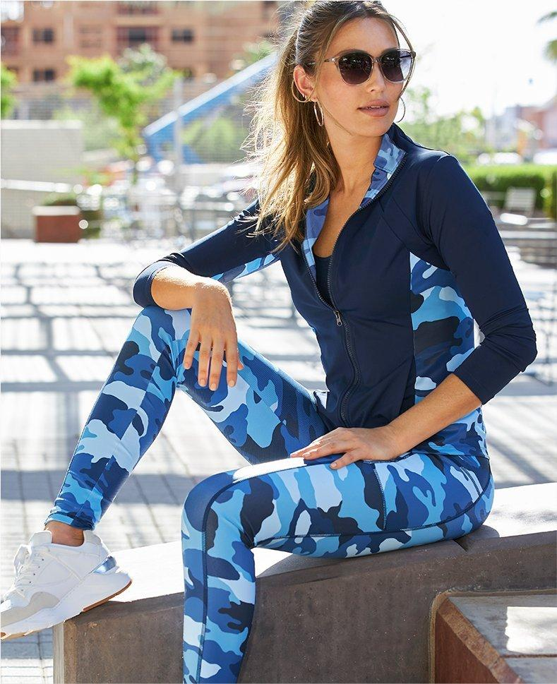 model wearing a blue camouflage warm-up and sunglasses.