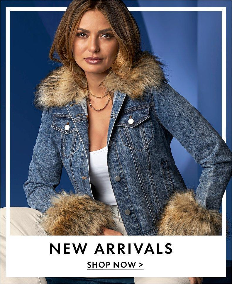 model wearing a jean jacket with brown faux fur collar and cuffs, white tank top, and off-white pants.