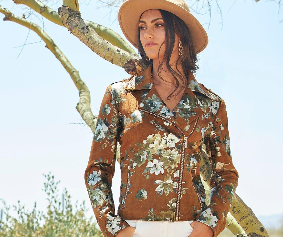 model wearing a brown moto jacket with silver foil florals all over, white jeans, and a tan fedora hat.