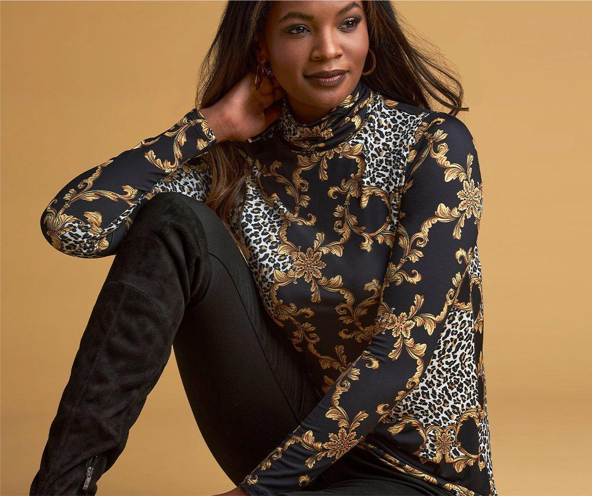 model wearing an animal status print long-sleeve turtleneck top and black leggings with black suede over-the-knee boots.