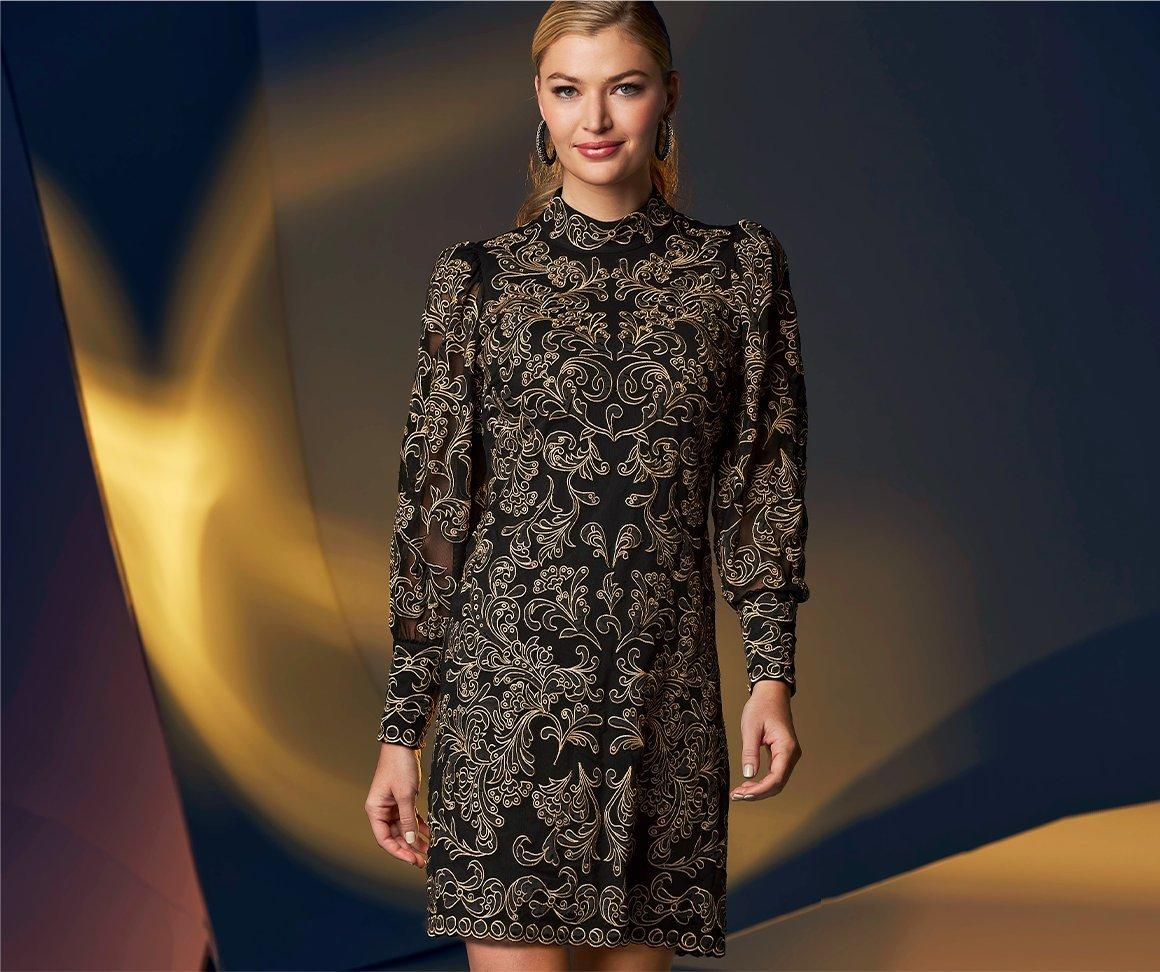 model wearing a black and gold lace overlay long-sleeve mock-neck shift dress.