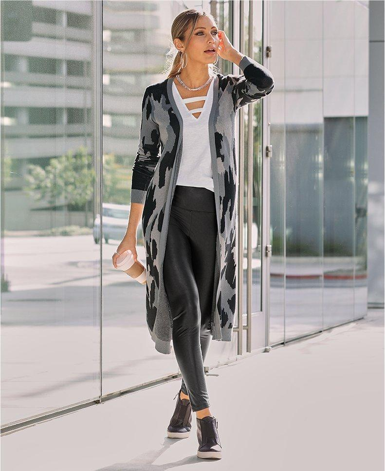 model wearing a gray camouflage sweater duster, white cutout tank top, black faux-leather leggings, and black wedge sneakers.