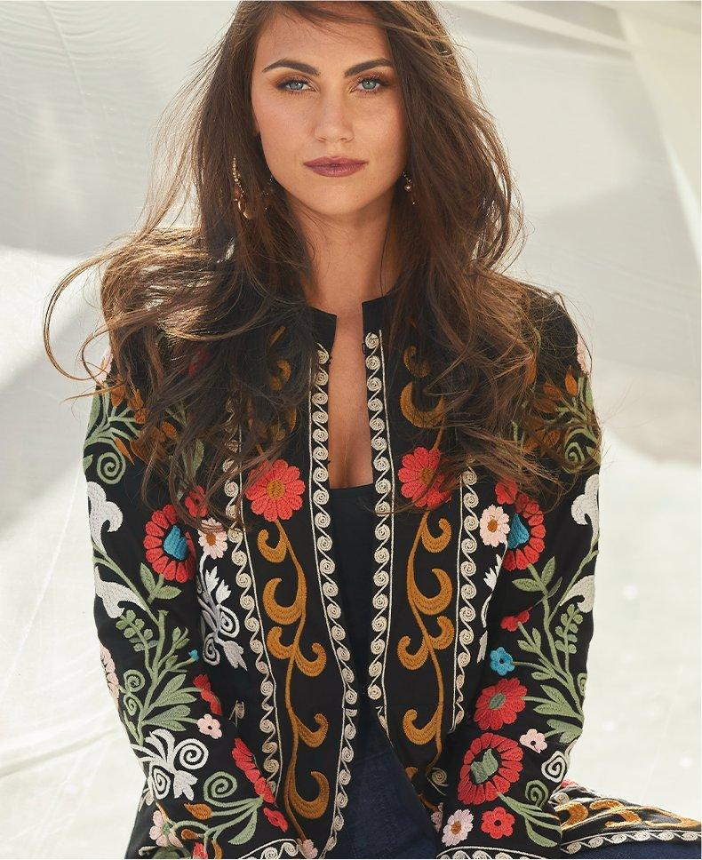 model wearing a black topper with multicolored embroidered flowers, black tank top, and jeans
