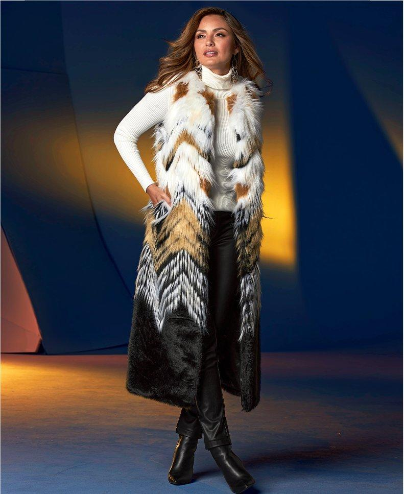 model wearing a multicolored faux fur long vest, white ribbed turtleneck sweater, black leggings, and black booties.