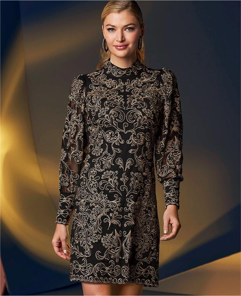 model wearing a black mock-neck long-sleeve dress with gold lace embellishment.
