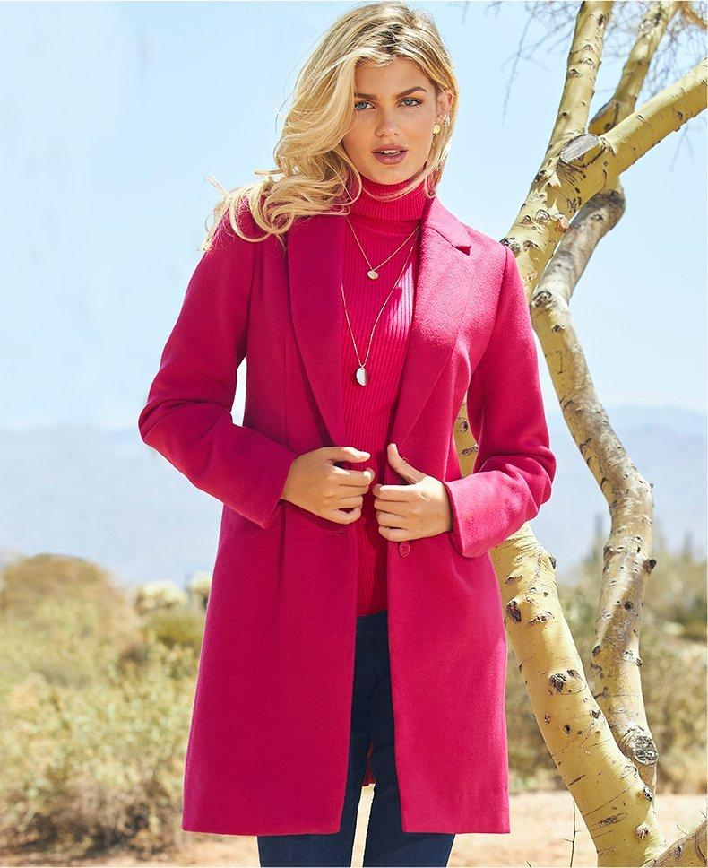model wearing a hot pink blazer, hot pink ribbed turtleneck sweater, and jeans.