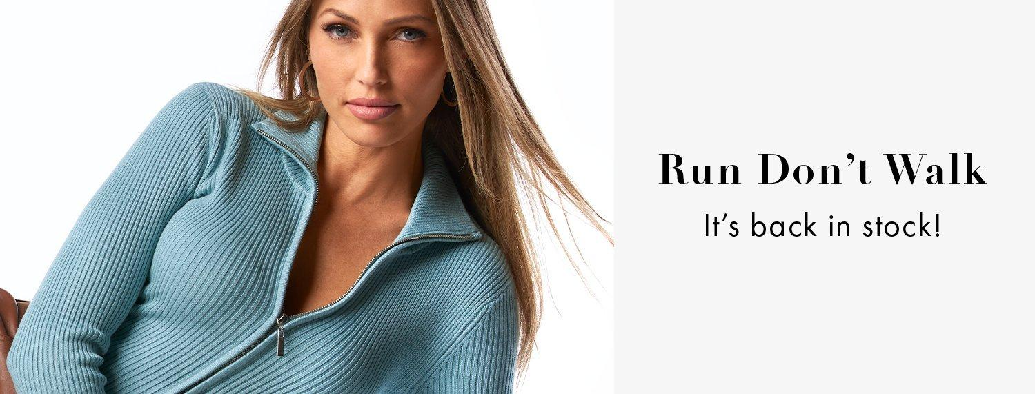 model wearing a light blue ribbed zip-up cardigan.