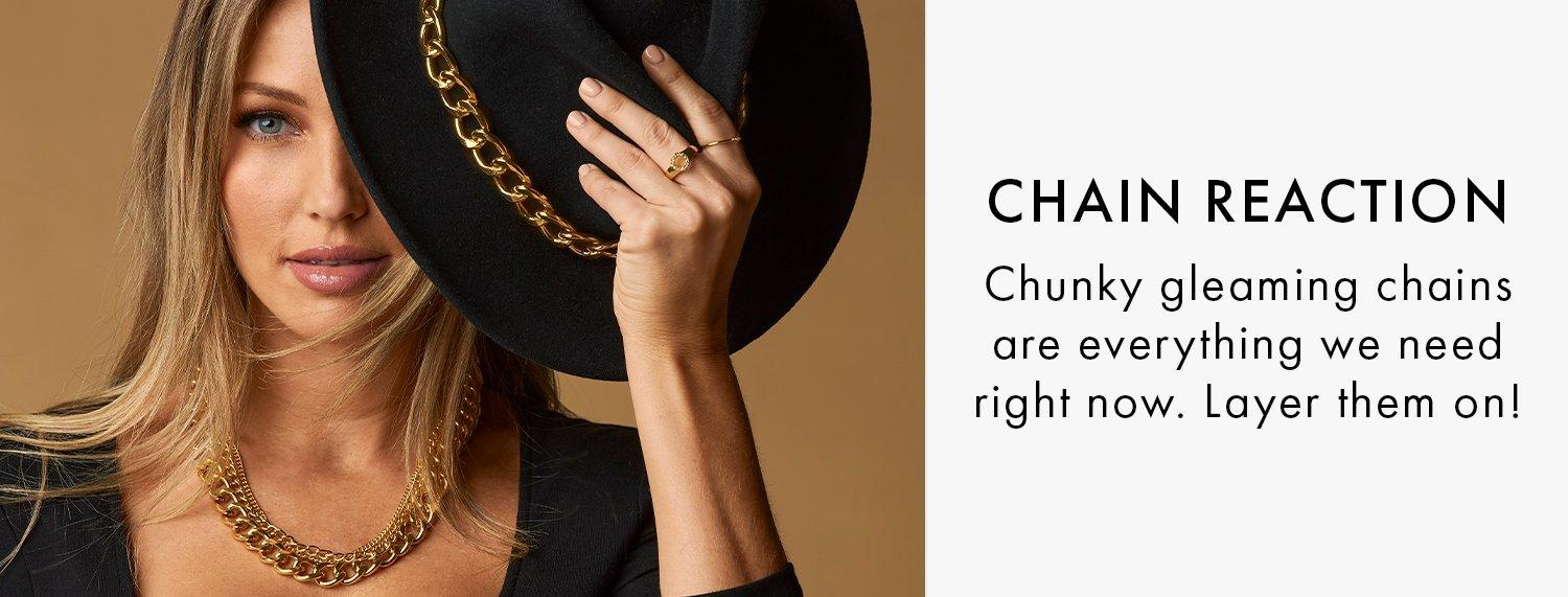 model wearing a black fedora hat with a gold chain, gold chain necklace, and black square-neck top.