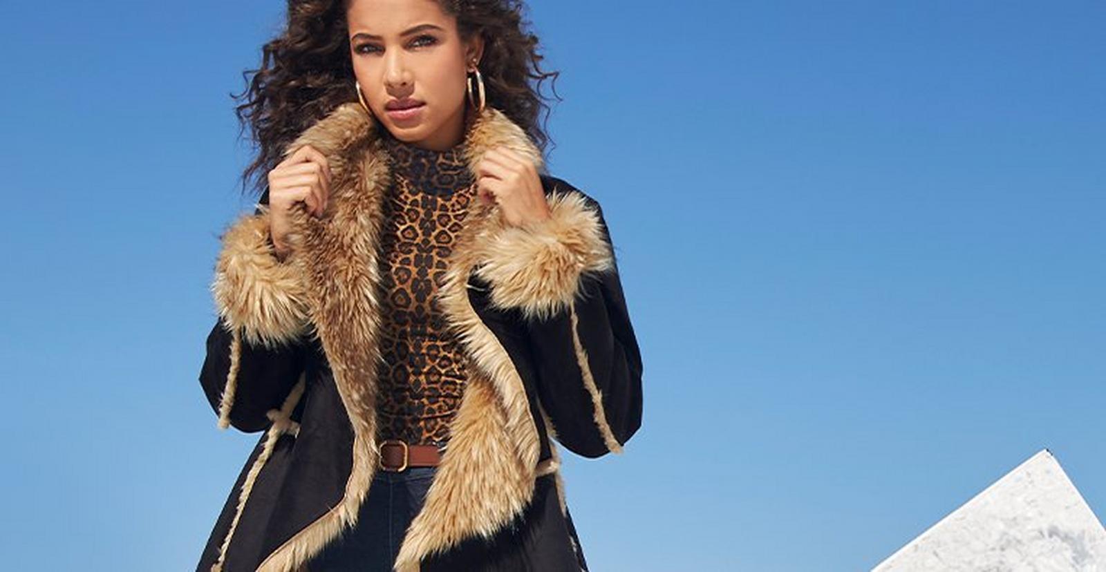 model wearing a black cascading long coat with tan faux fur, silver hoop earrings, and brown animal print turtleneck top.